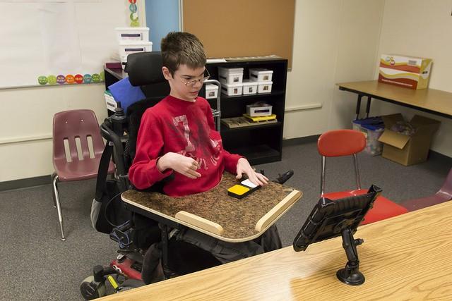 Persoon in rolstoel maakt gebruik van de Blue2 Bluetooth Switch om een iPad te bedienen